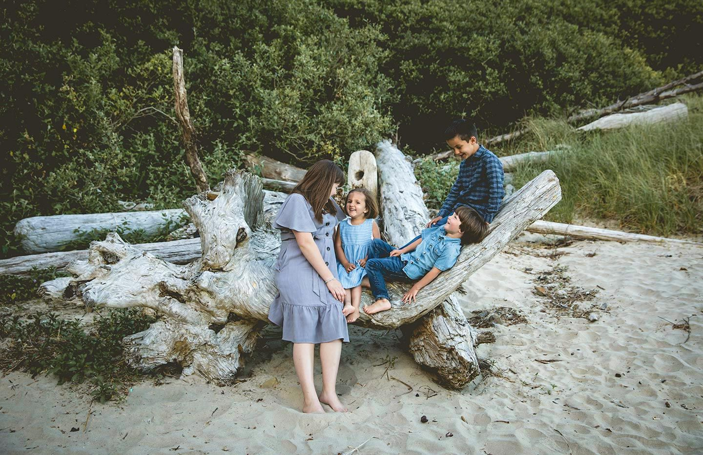 four siblings sitting and laying on a large piece of driftwood on the beach