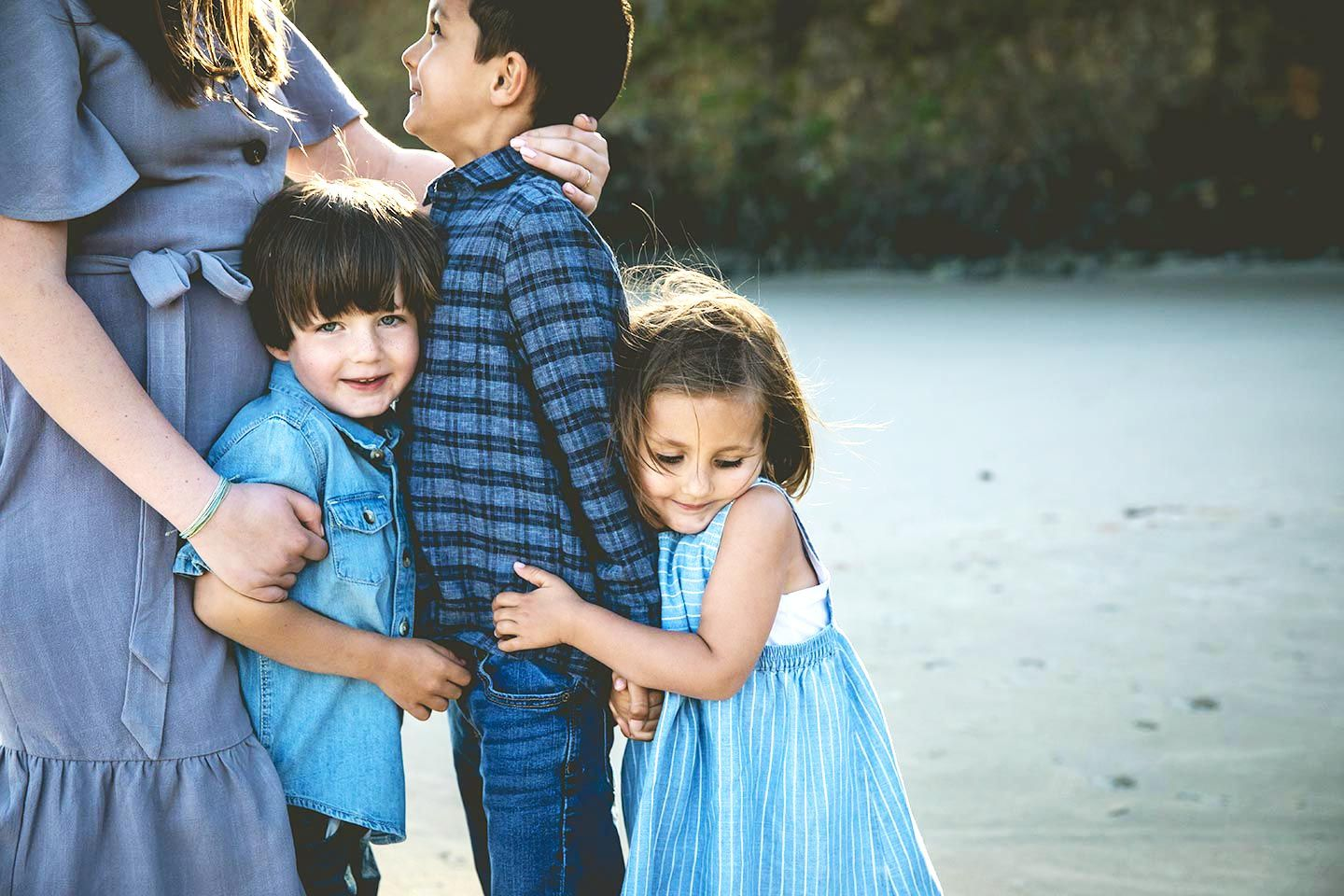 siblings stacked in a big hug on the Oregon coast