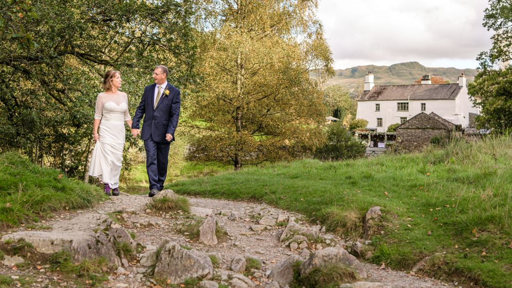 Newly weds walking down to Rydal Water after Cote How wedding