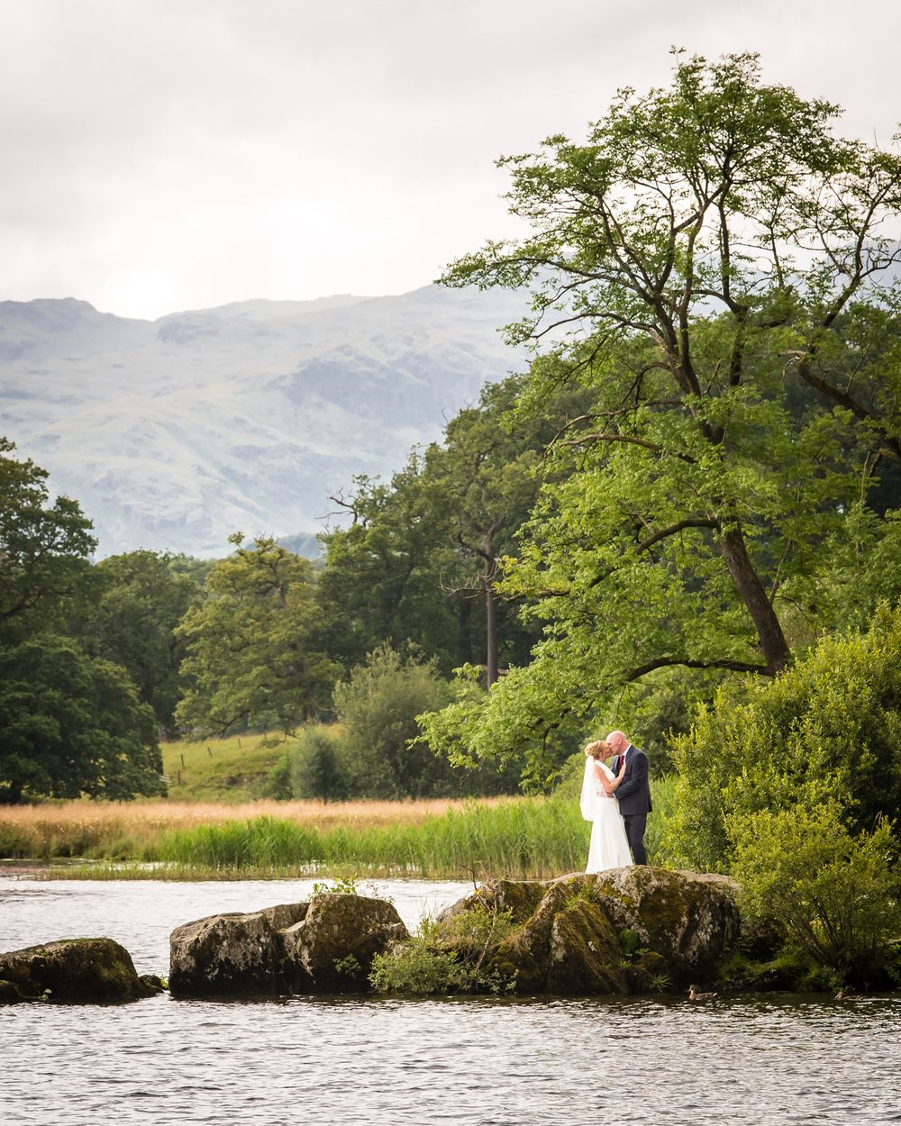Bride and groom on rocky outcrop beside Windermere
