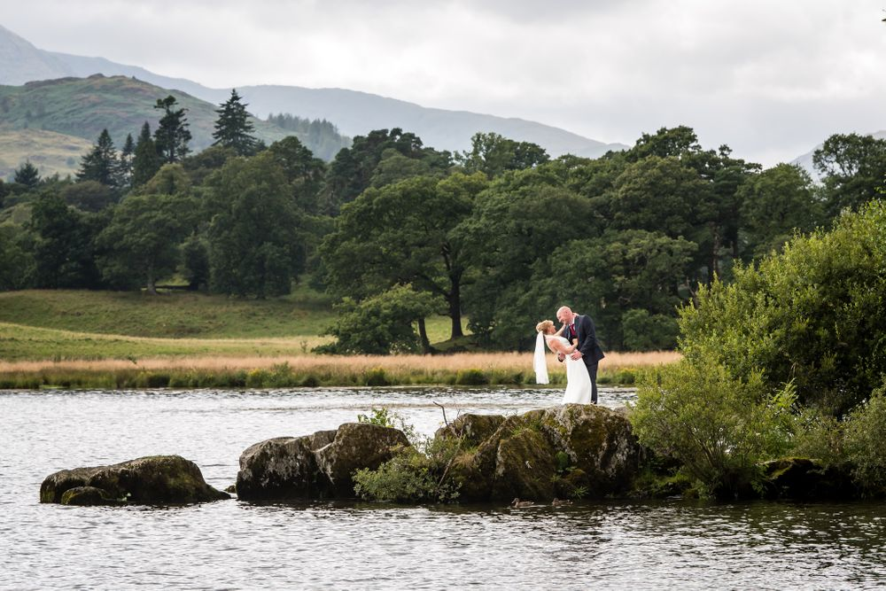 Bride and groom with fells in background at Windermere
