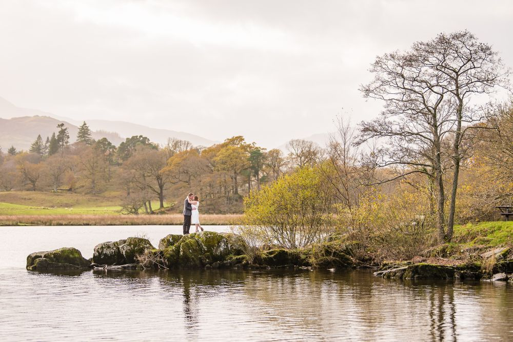 Couple on rocky outcrop beside Windermere in Lake District