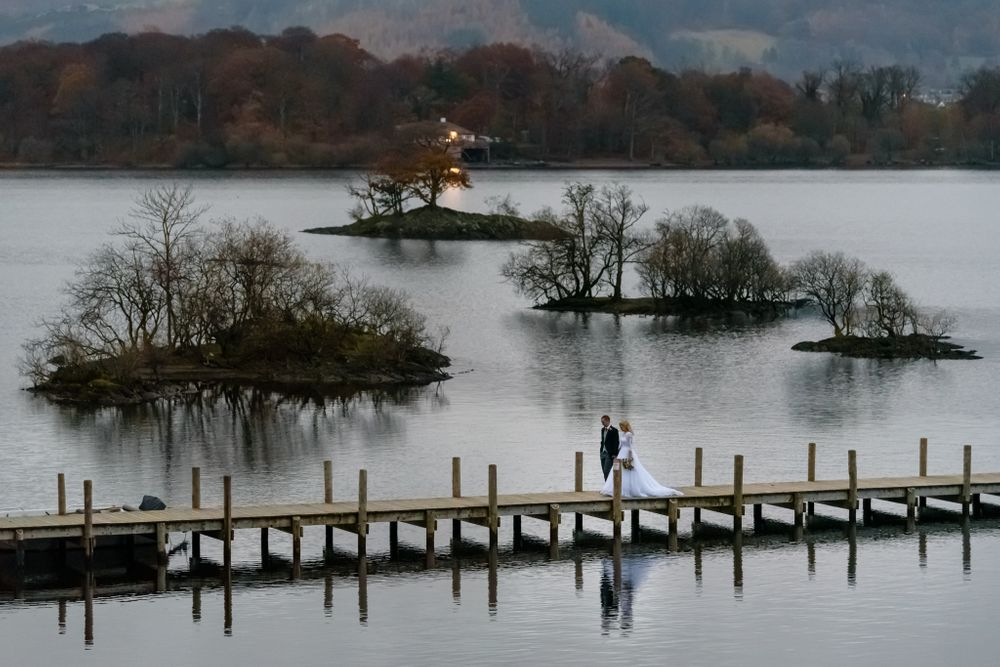 Bride and groom in distance on Lingholm Estate jetty on Derwentwater