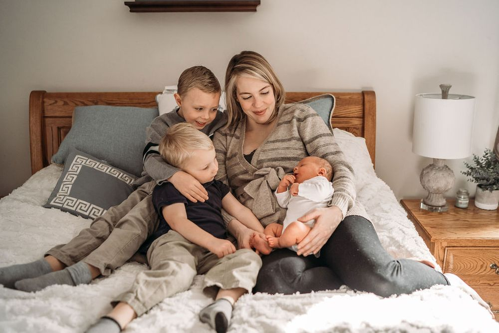 mom holding her three boys in her boston bedroom