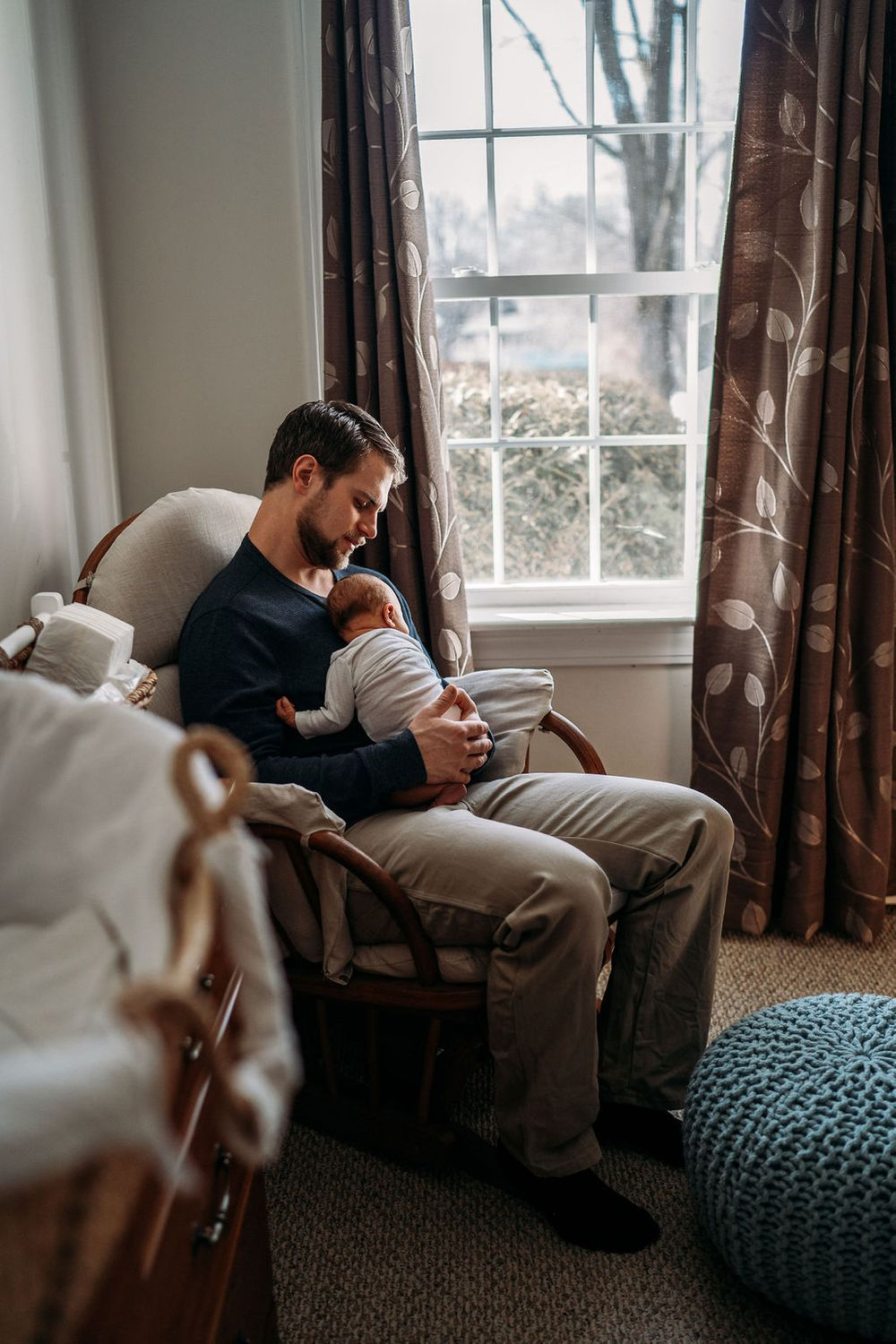 dad rocking his newborn in the nursery of their boston home