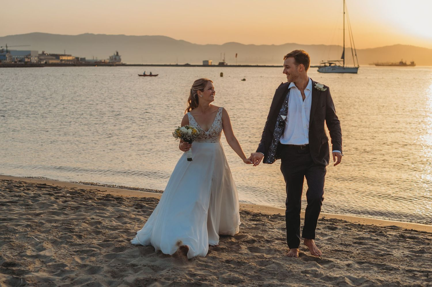 Groom and bride walking on beach in Gibraltar