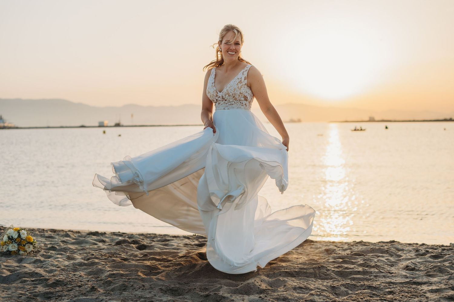 Bride dancing on beach in Gibraltar