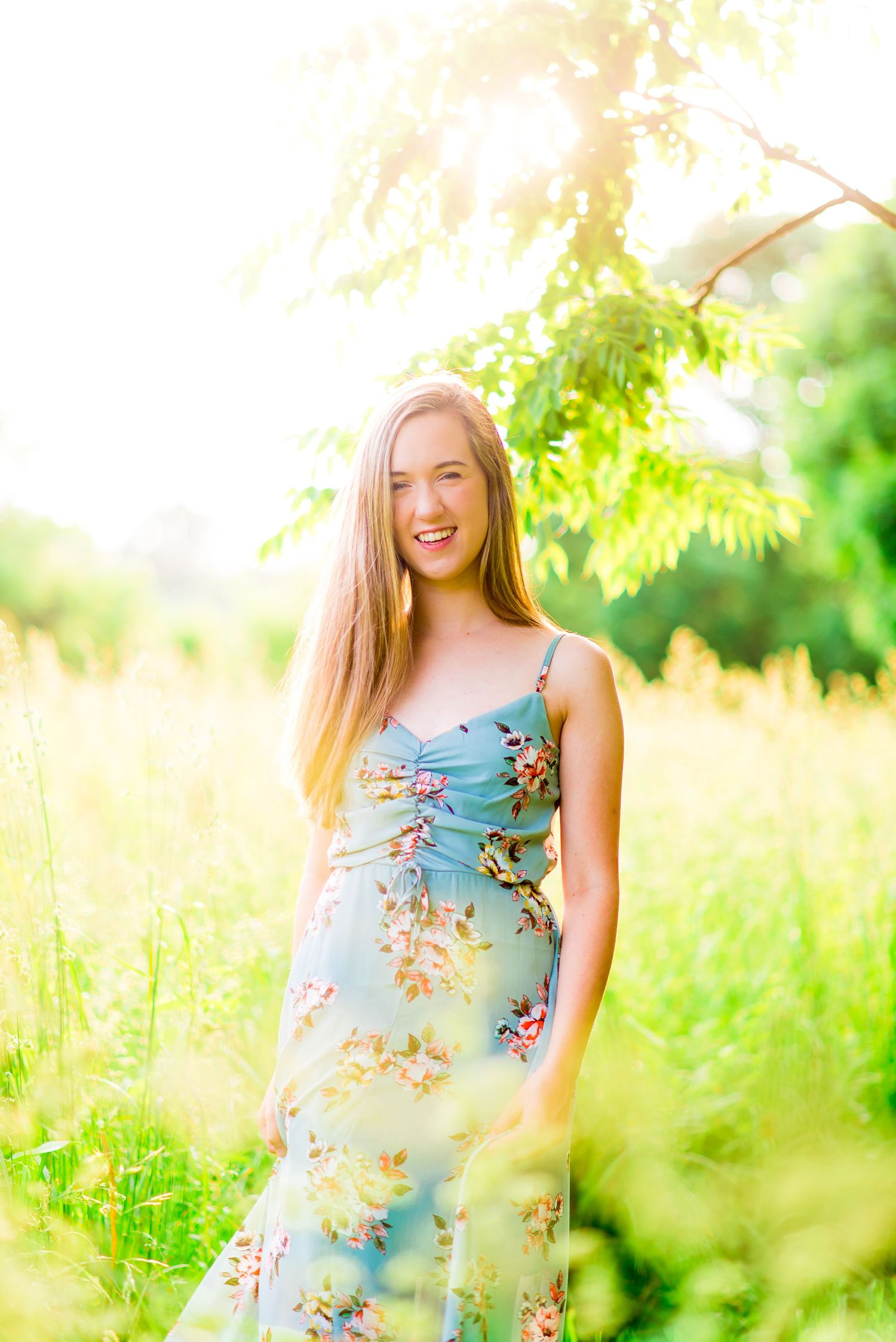 high school senior smiles in blue floral dress at sunset at Montrose Harbor in Chicago