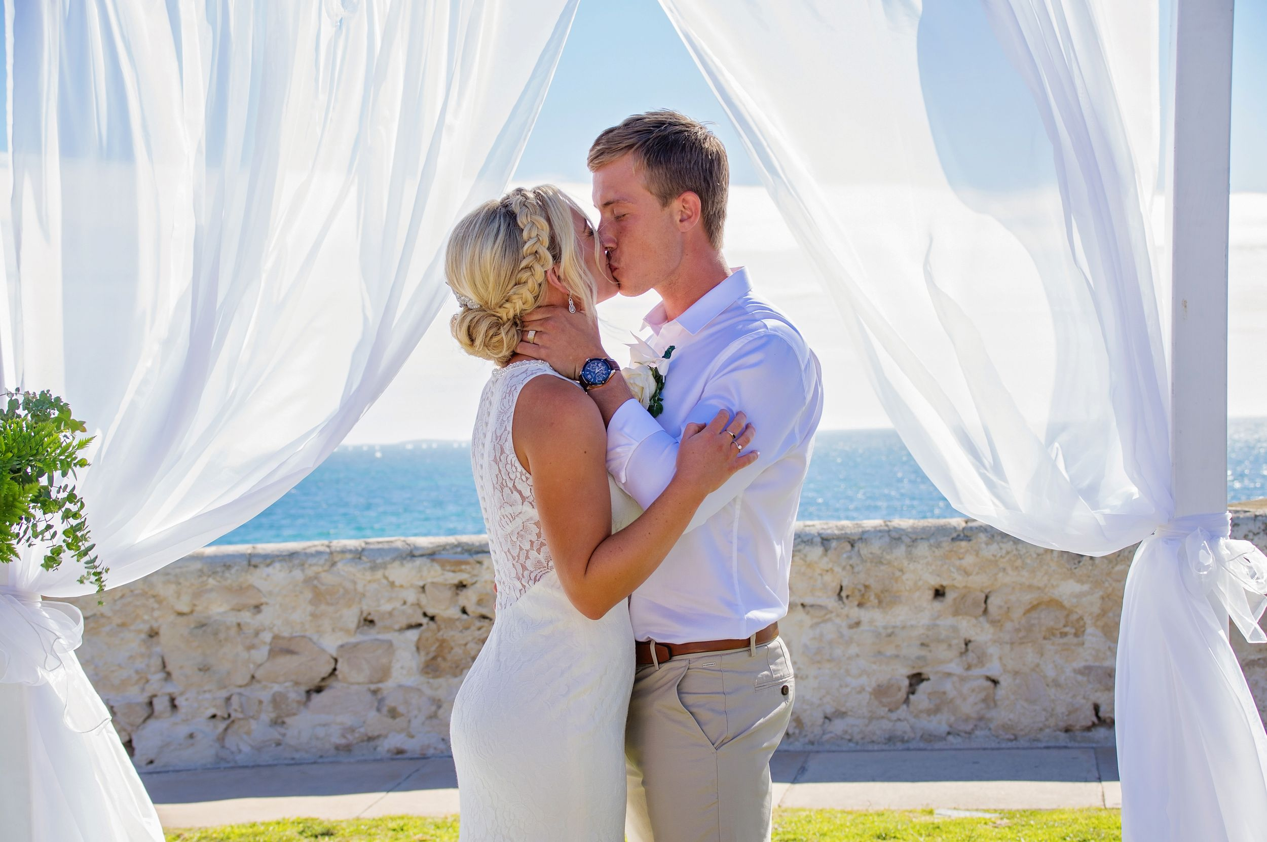 bride and groom kissing outdoor beach location