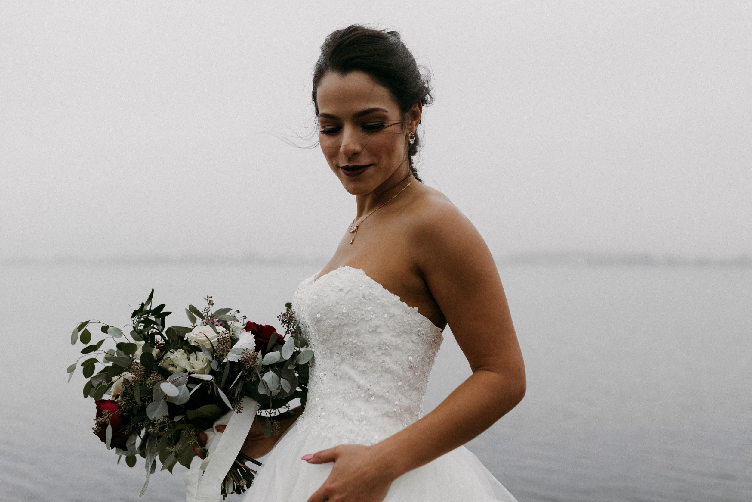 PEI bride in her wedding dress with her bouquet on foggy Victoria Park boardwalk looking down and smiling.