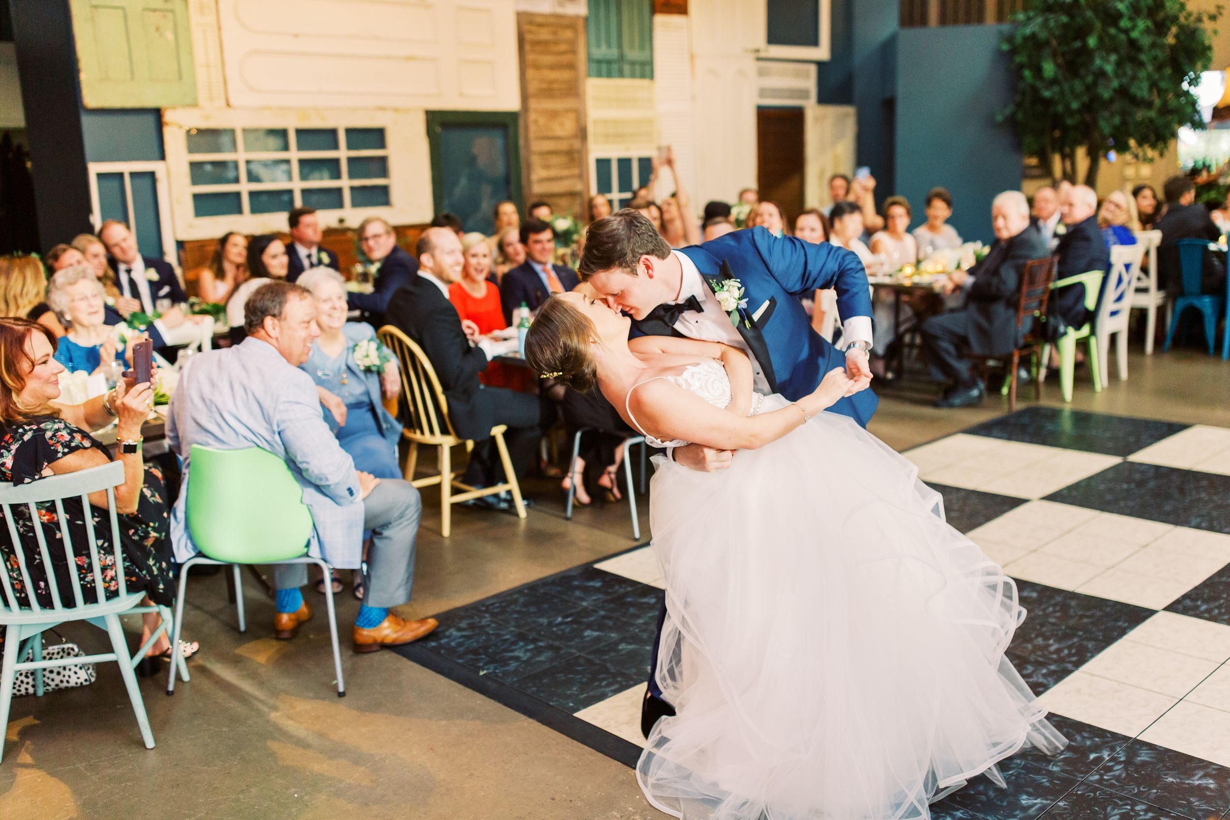 bride and groom dip kiss during their first dance at their soho south cafe wedding reception in savannah, ga