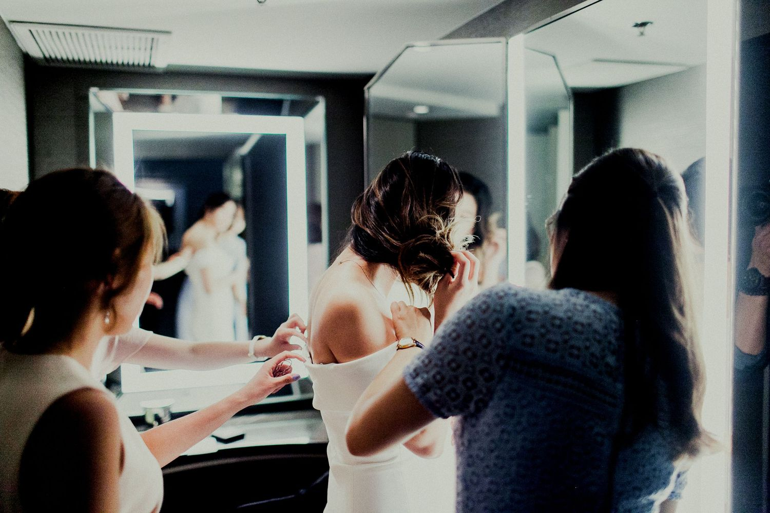 bride adjusting hair in front of mirror with friends helping