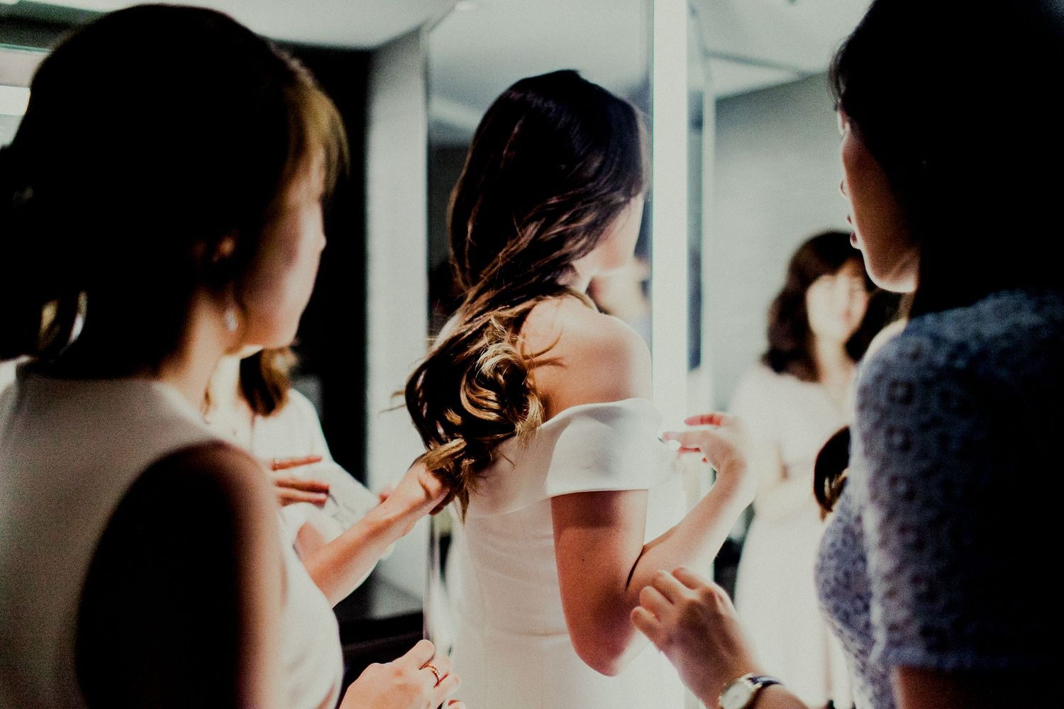 friends adjusting dress while bride getting ready