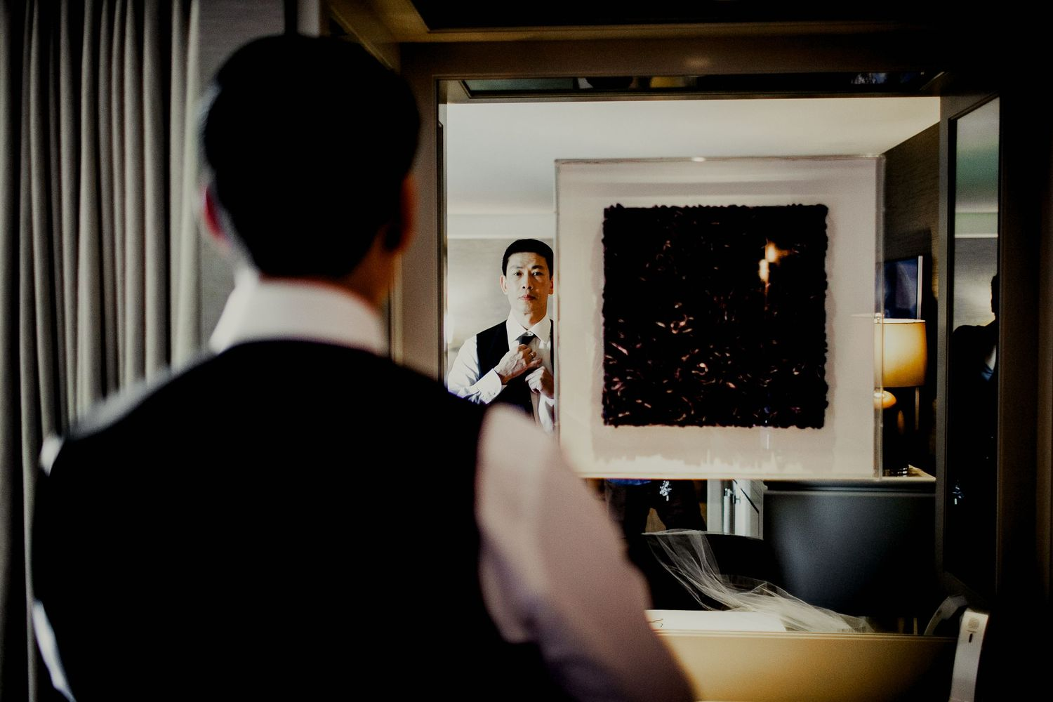 groom adjusting suit in front of mirror