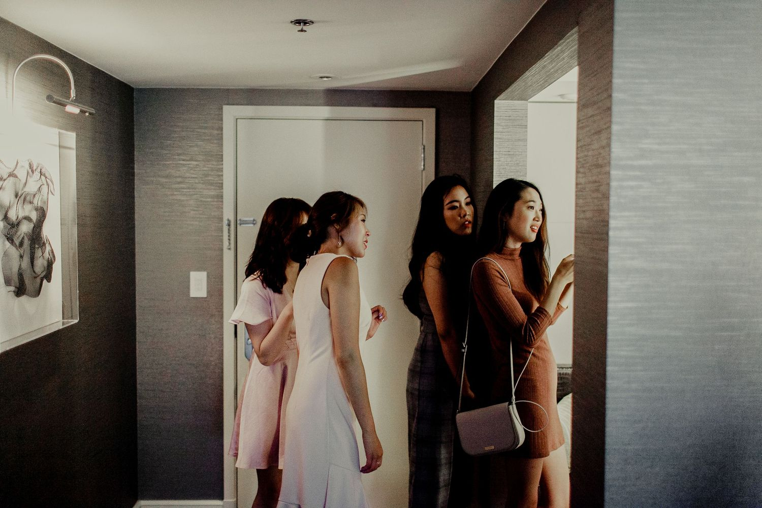 bridal party watching and helping bride prepare makeup and hair inside hotel