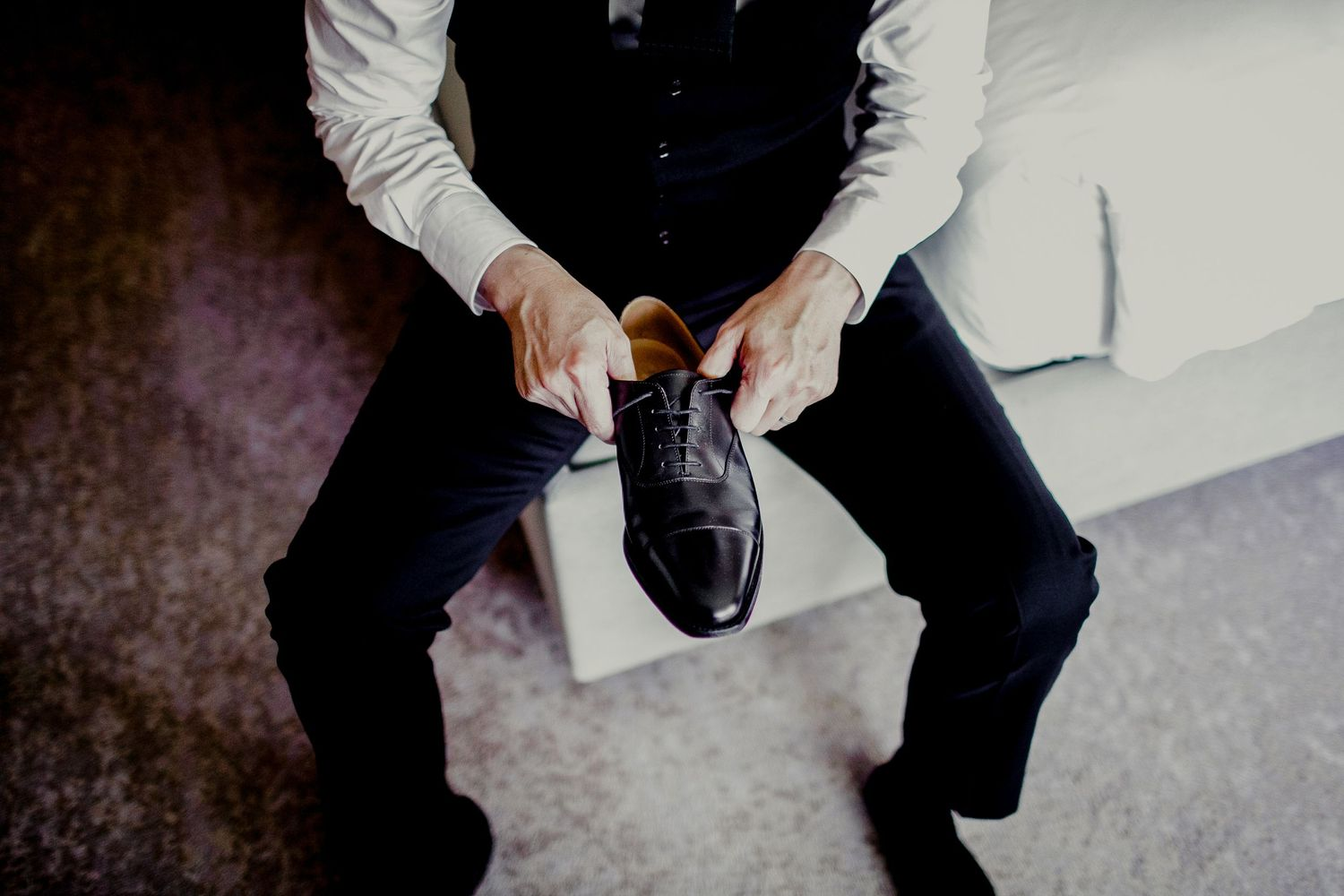 groom adjusting shoes to put on