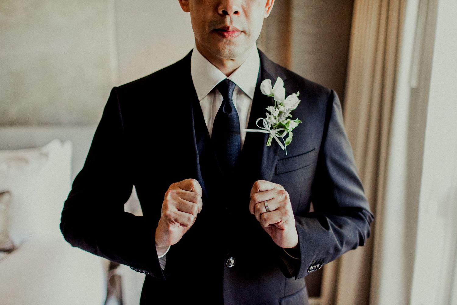 groom showing wedding ring and suit