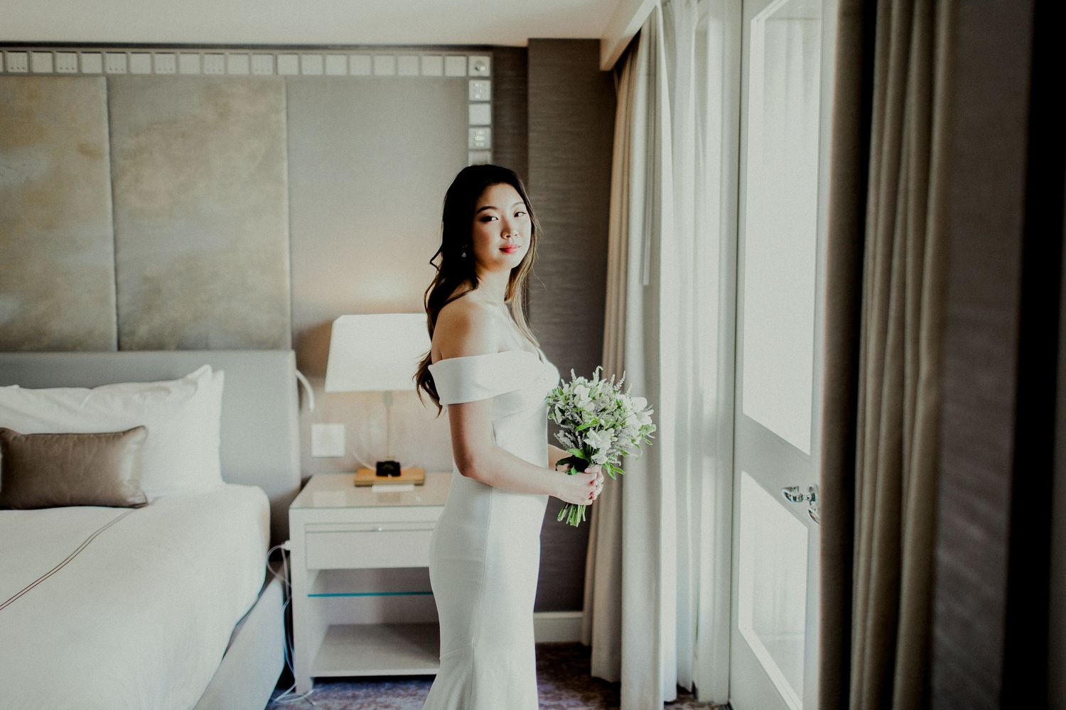 bride standing in front of window holding flowers