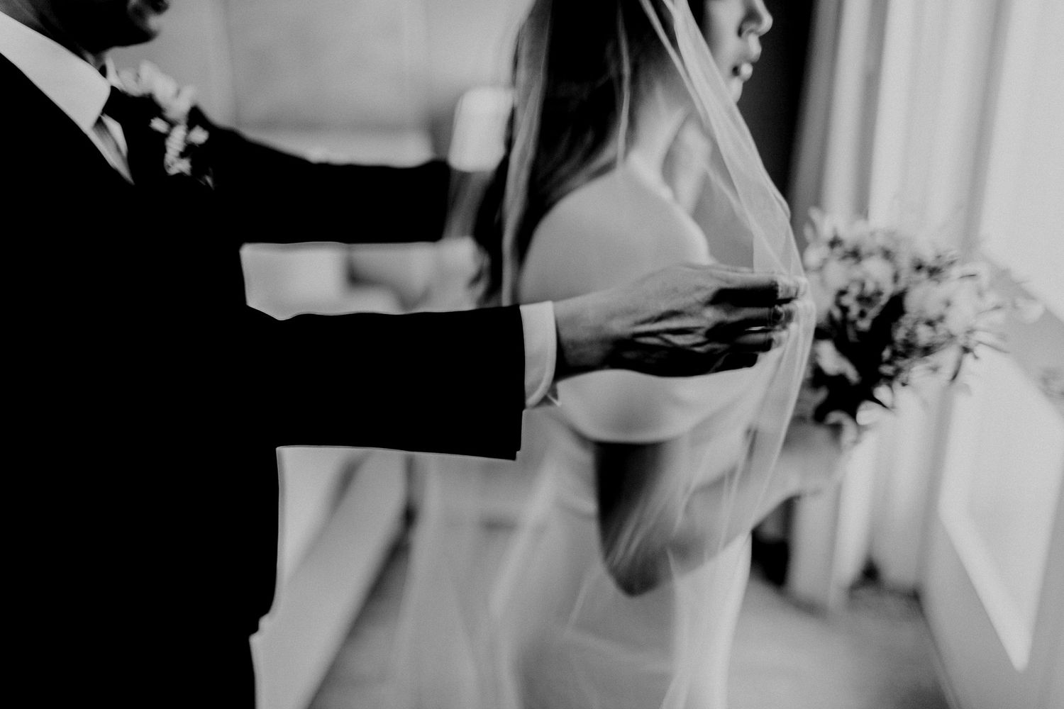 groom adjusting veil for bride in front of a mirror