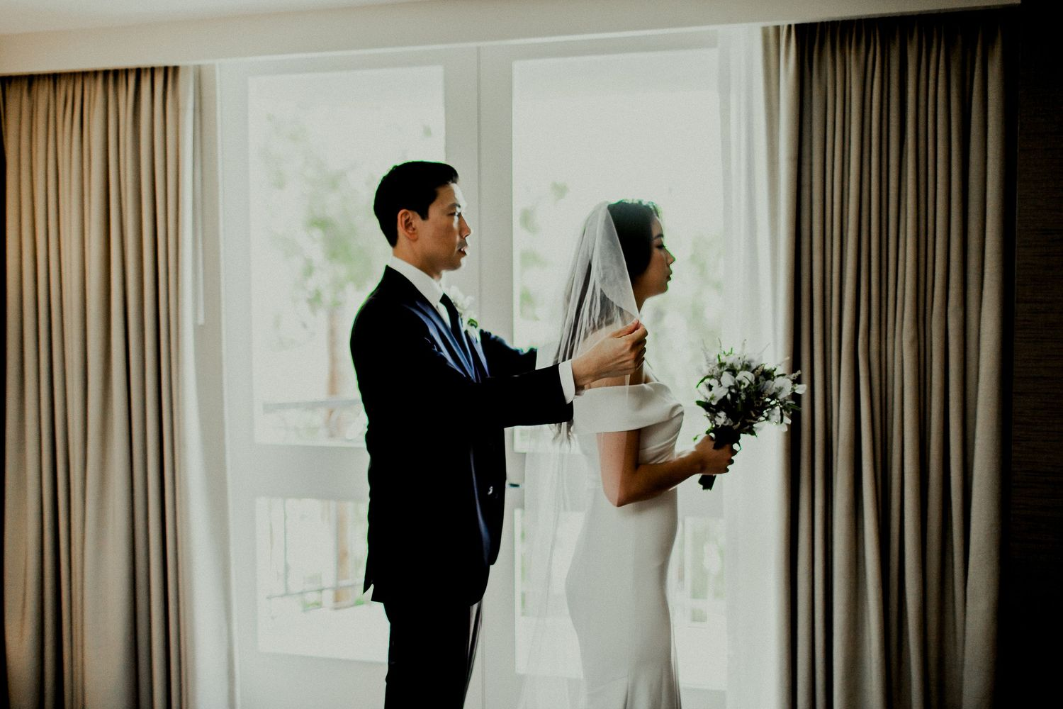 groom adjusting veil for bride in front of balcony window