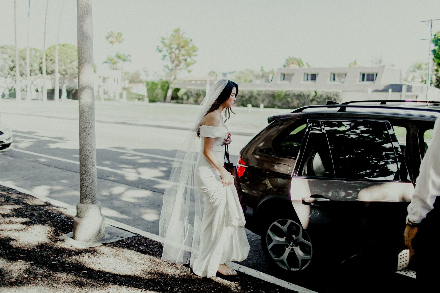 bride entering car heading to ceremony and reception venue