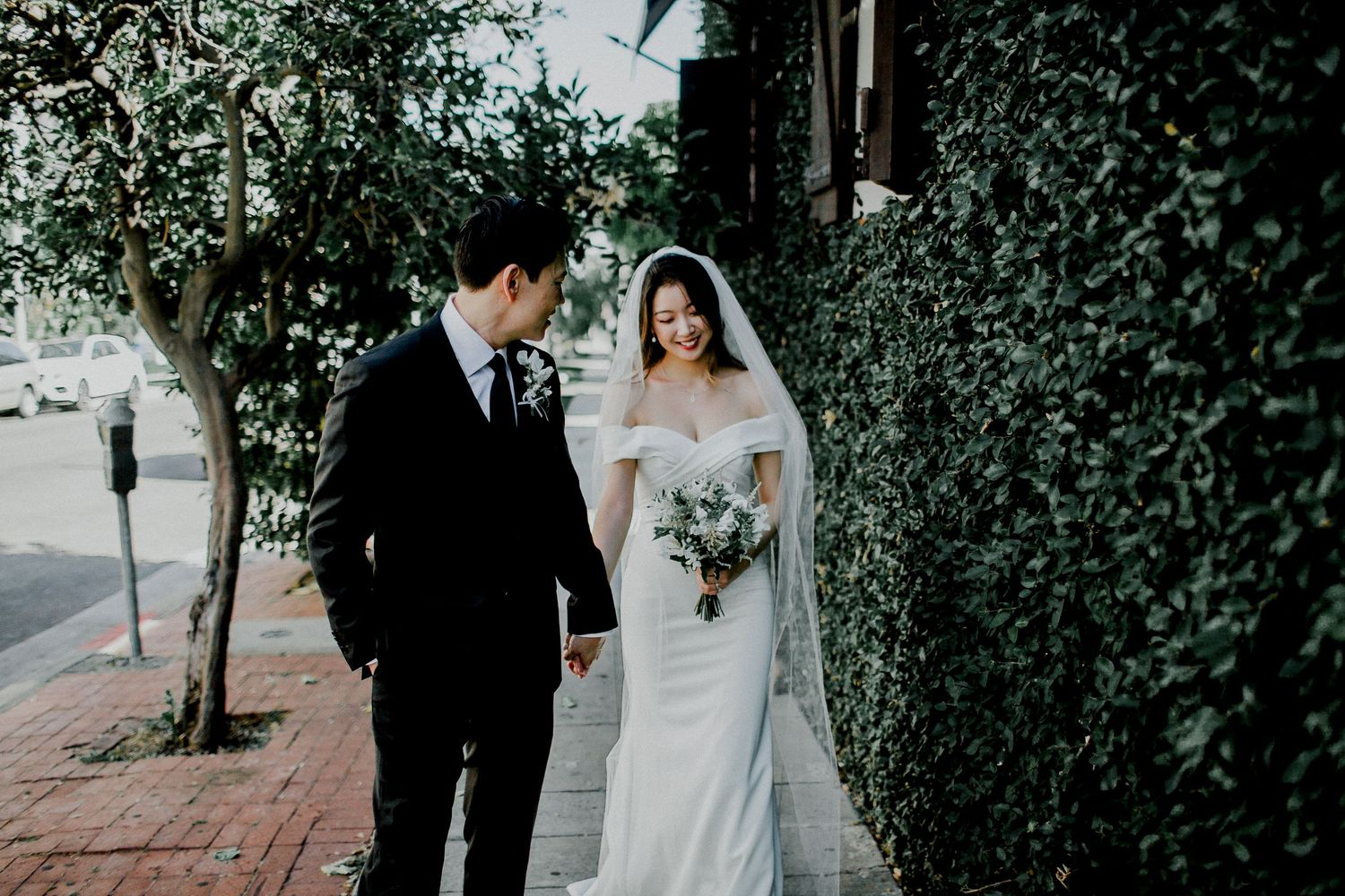 bride and groom walking on sidewalk with leaf wall side of a.o.c. la