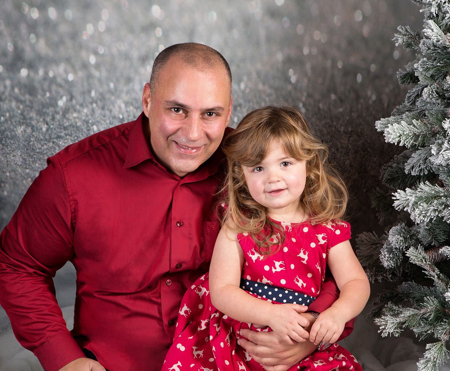 Festive self portrait of photographer Paul Baybut and his daughter against a silver bokeh backdrop and Christmas tree