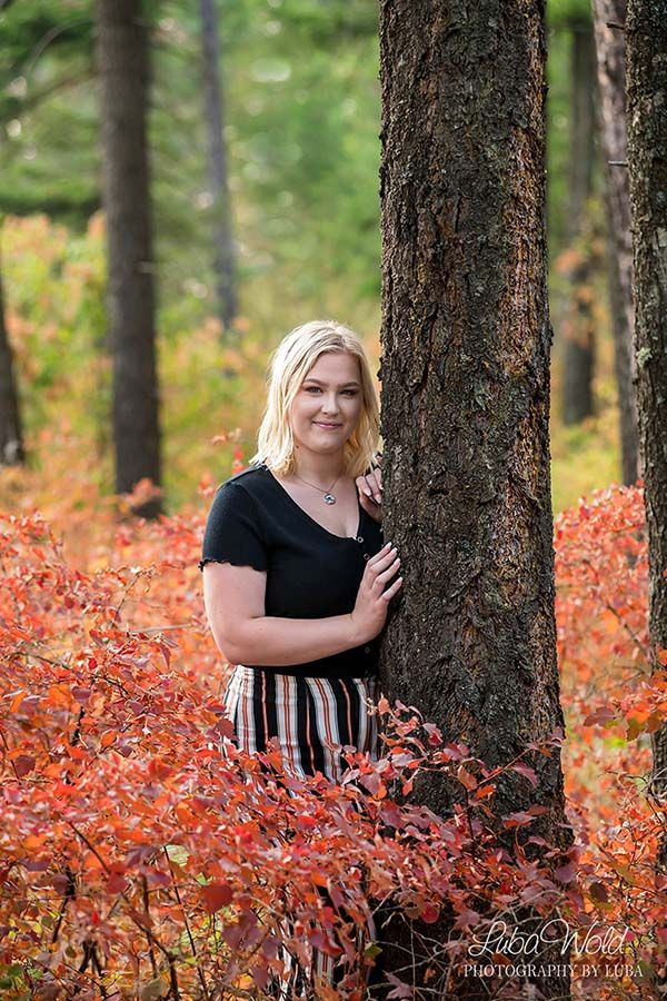 Coeur d Alene high school senior girl photographer luba wold standing in fall tree woods casual outdoor