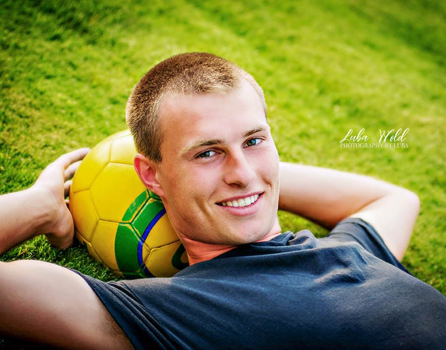 Spokane high school senior boy with football photographer luba wold laying on a grass taken in Coeur d Alene