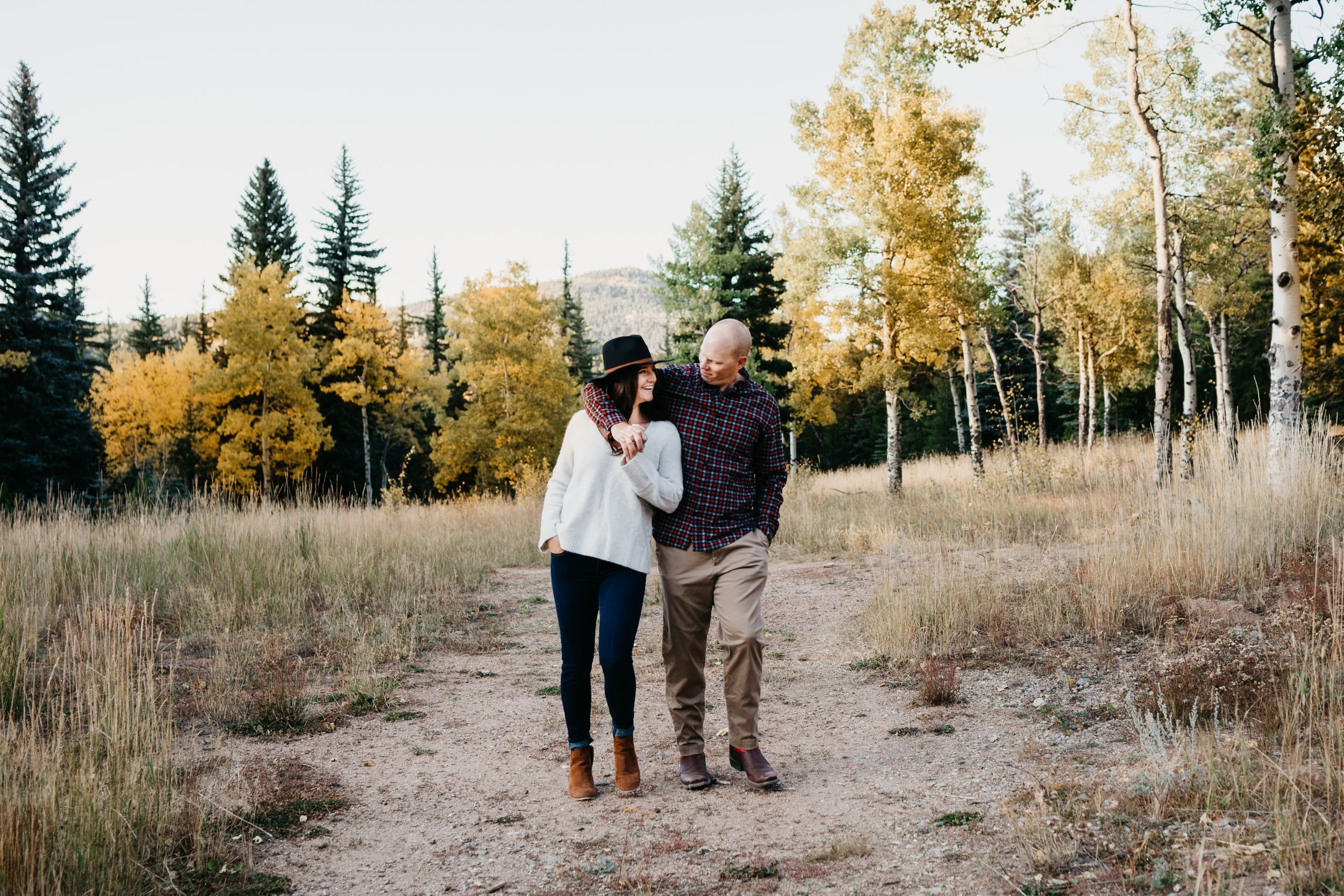 Beautiful sunny mountain field and trees Engagement session Colorado stylish