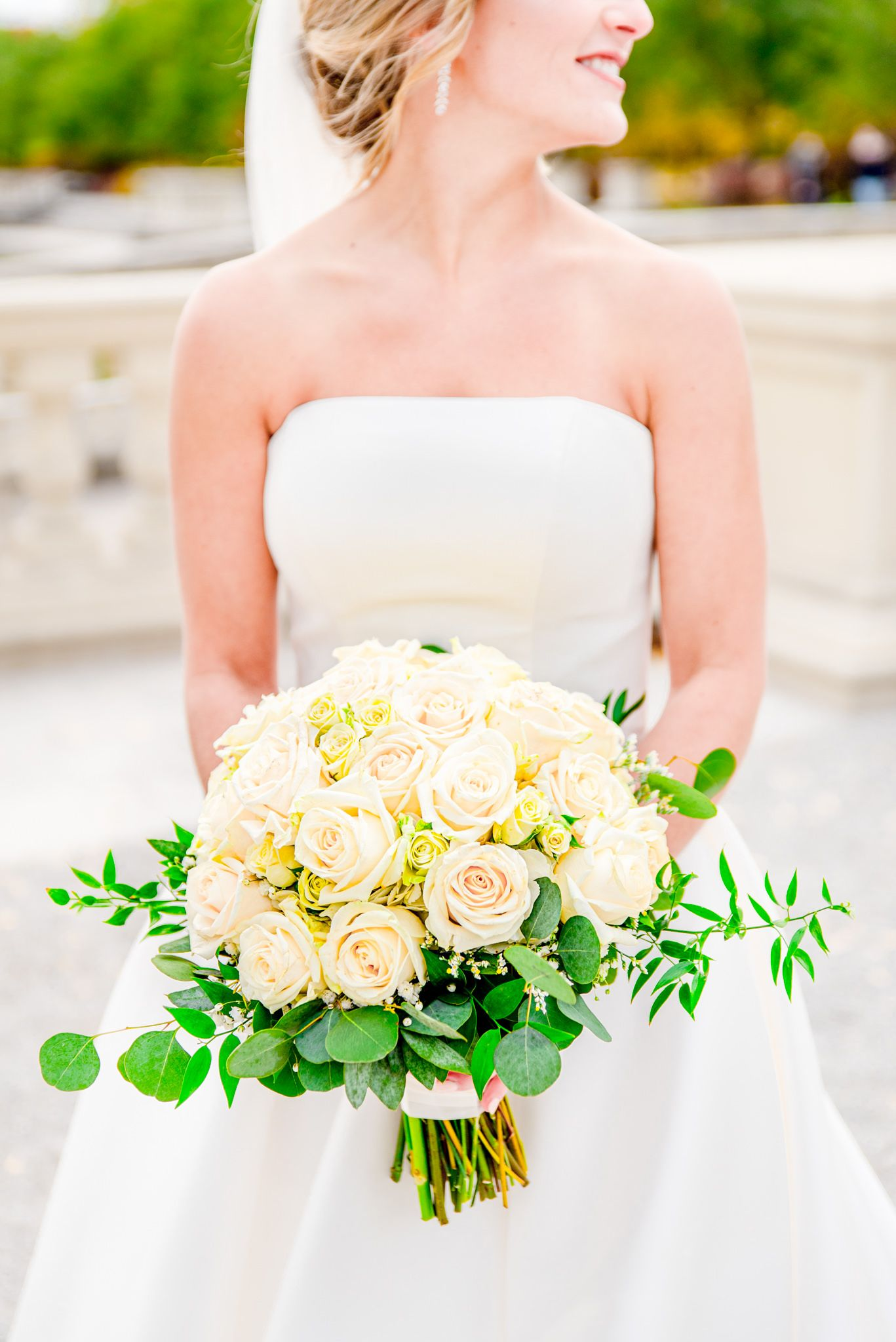 bride in strapless wedding dress holding white and green bouquet, looking to the side