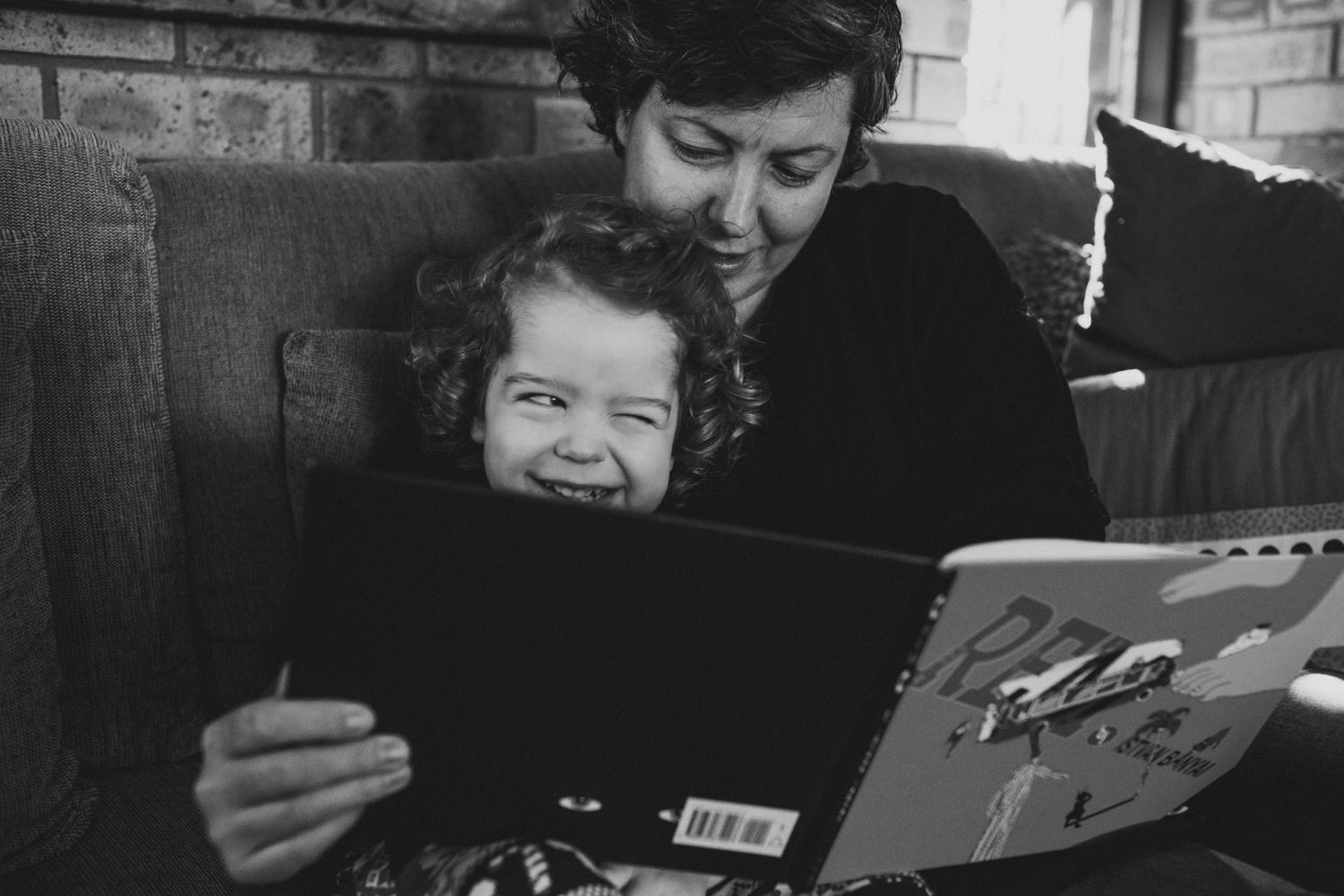 Child pulling funny face while his Mum reads to him