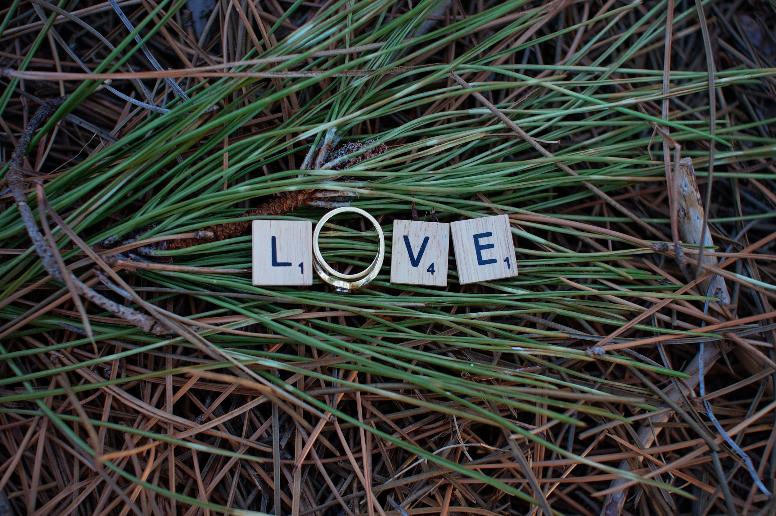 letters spelling out love with engagement ring