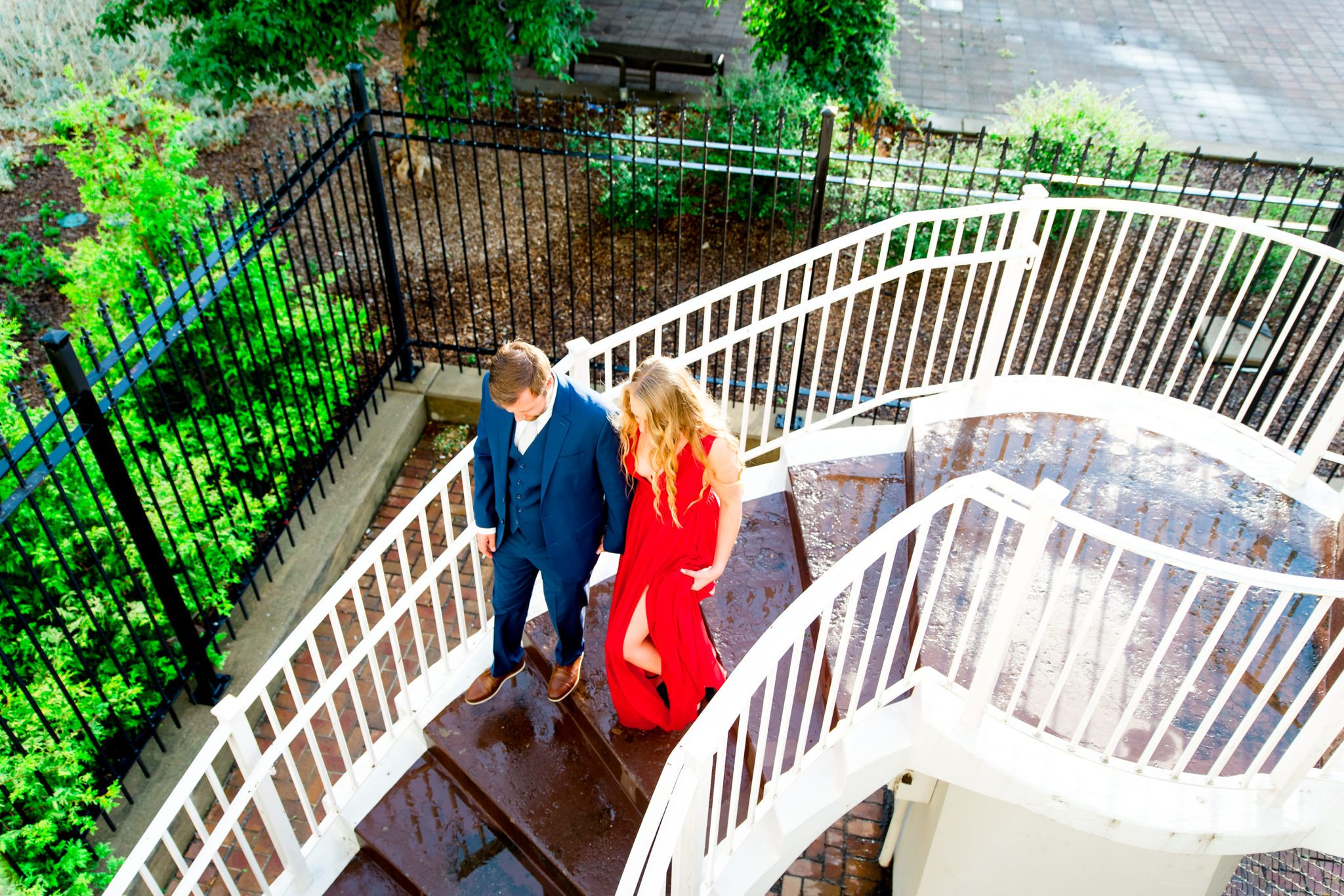 woman in red dress and man in navy suit walk down white staircase wet with rain at the Galt House Hotel