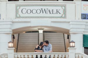 couple kissing at the steps of coco walk during an engagement session in coconut grove Florida