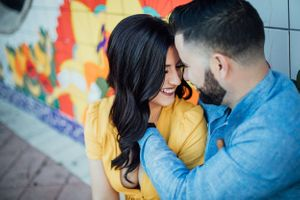 couple smiling at each other during an engagement session in Calle Ocho Miami Florida