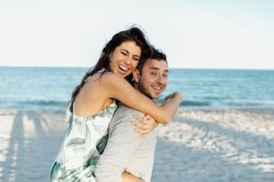 couple smiling as man gives woman a piggy back ride during engagement session in Miami Beach Florida