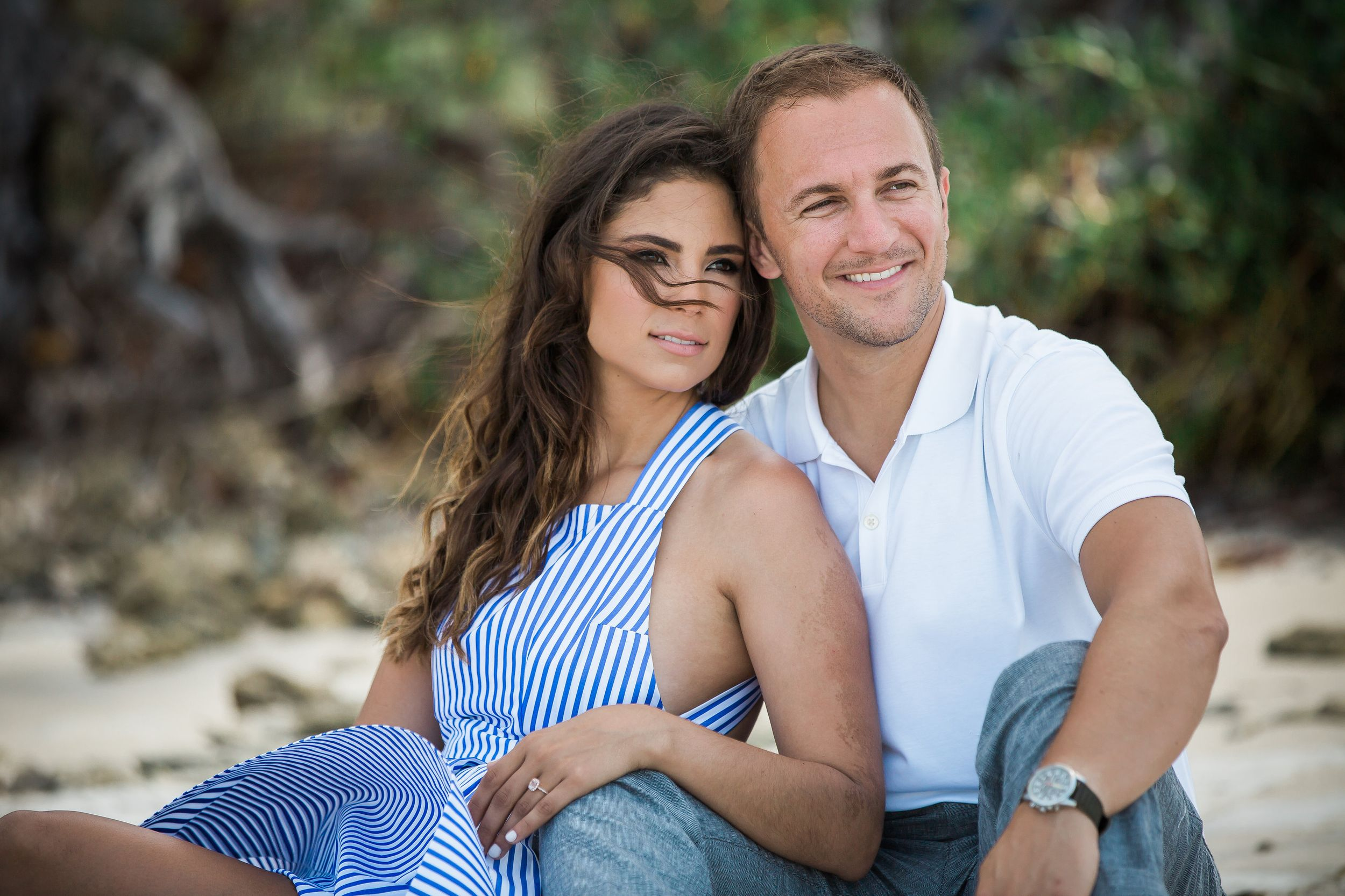 couple sitting on the sand looking in the ocean during an engagement session at Virginia key park in Key Biscayne