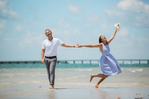 Couple walking on the beach while woman dances with her arm in the air during engagement session at Virginia key park