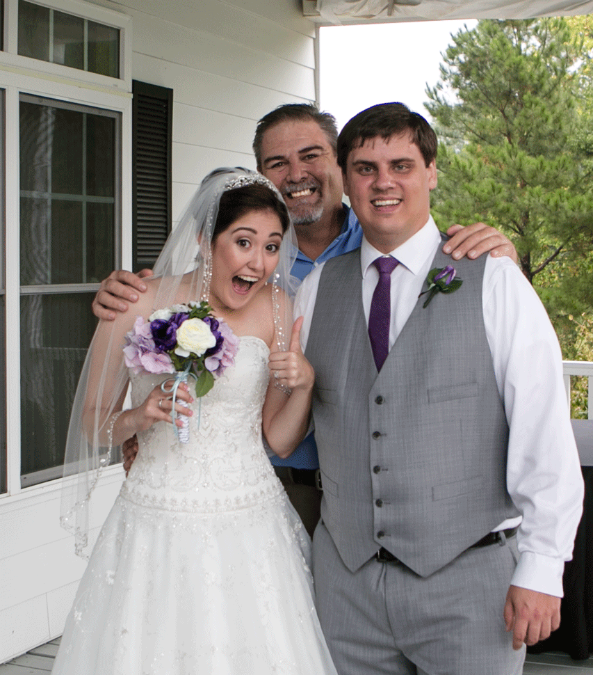 Photographer Les Hanna poses with newlywed bride and groom on their wedding day