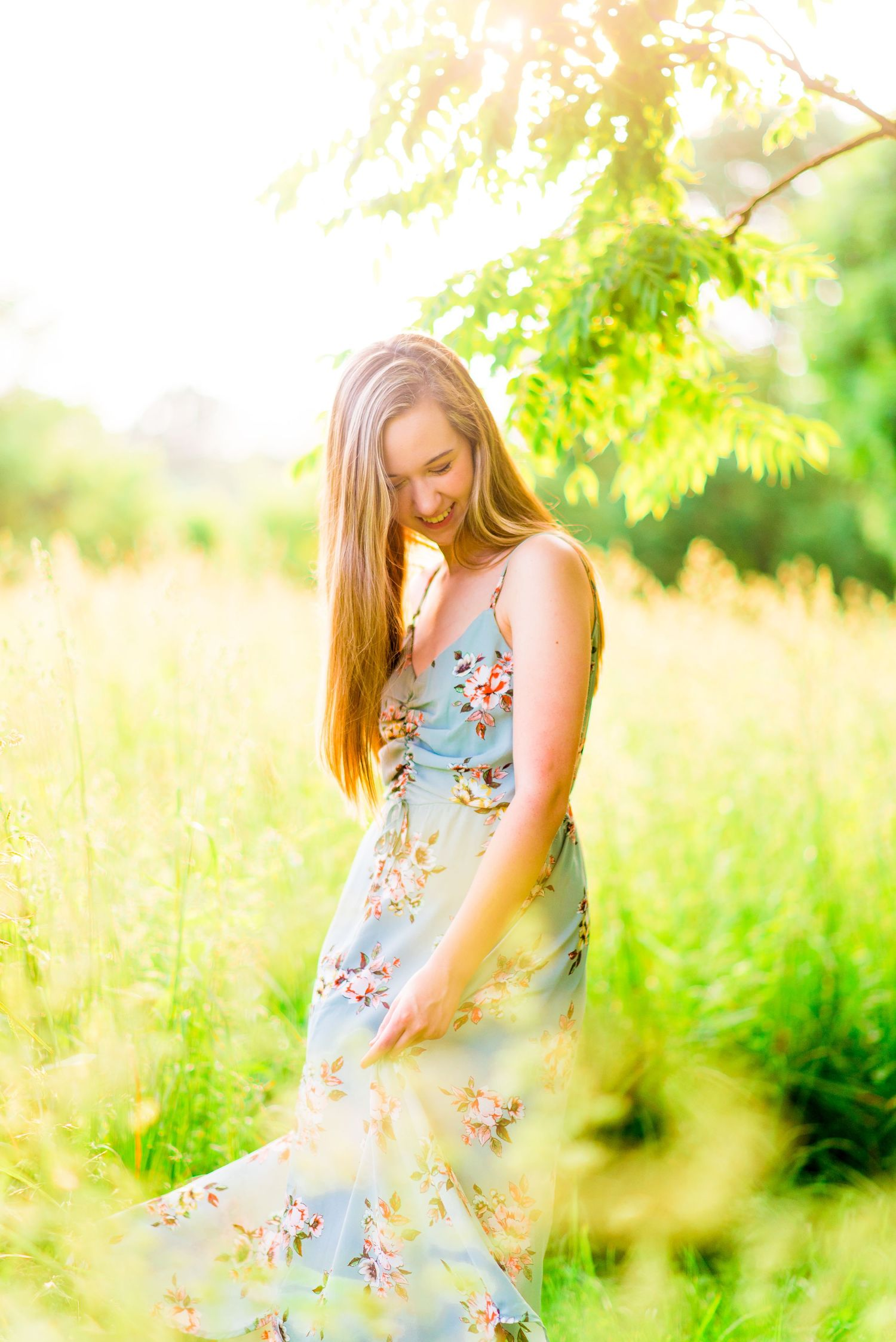 high school girl in blue floral dress dancing in field of tall grass at sunset at Montrose Harbor Chicago