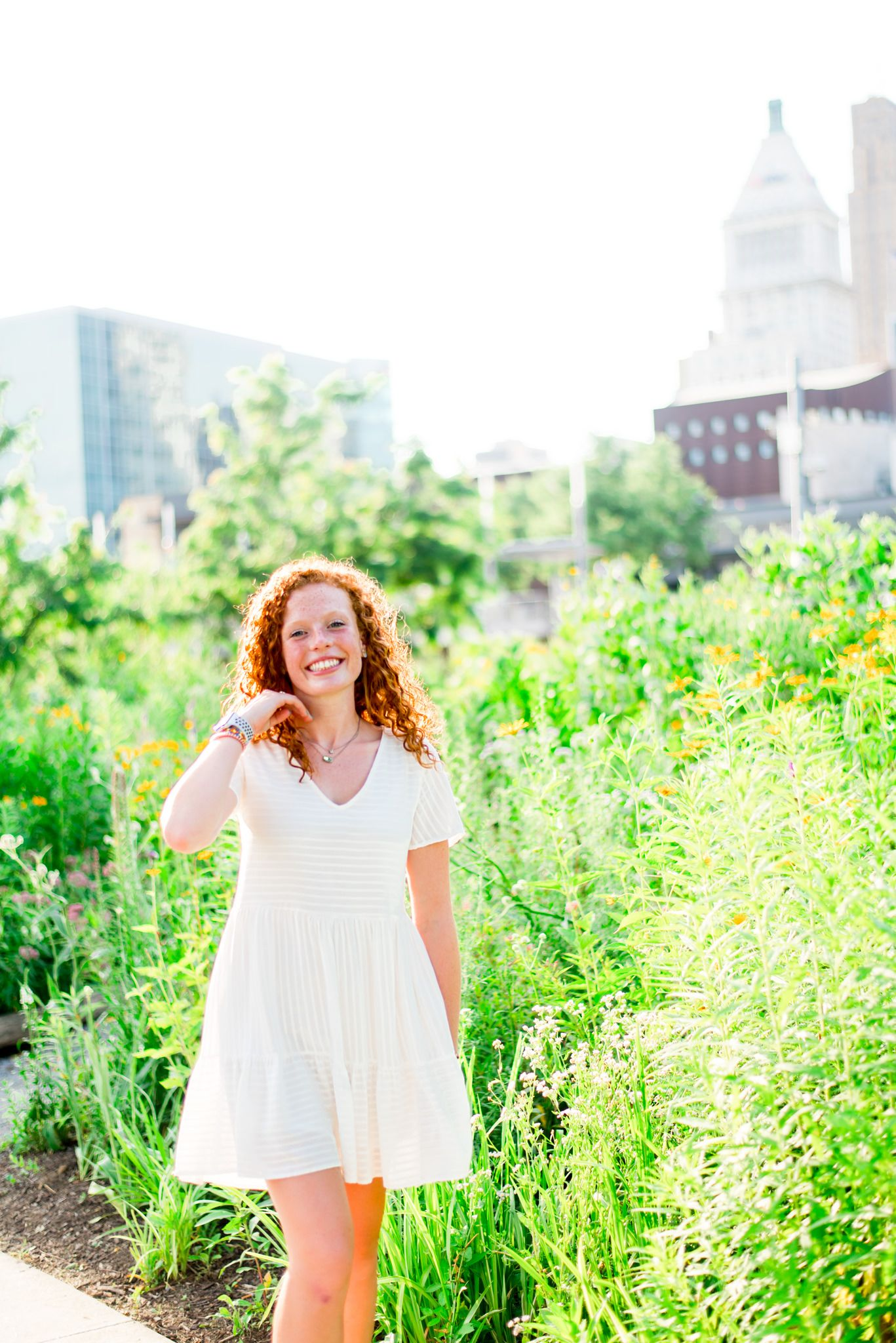 young woman in white dress flips her hair back in front of flowers and cityscape at Smale Park senior pictures
