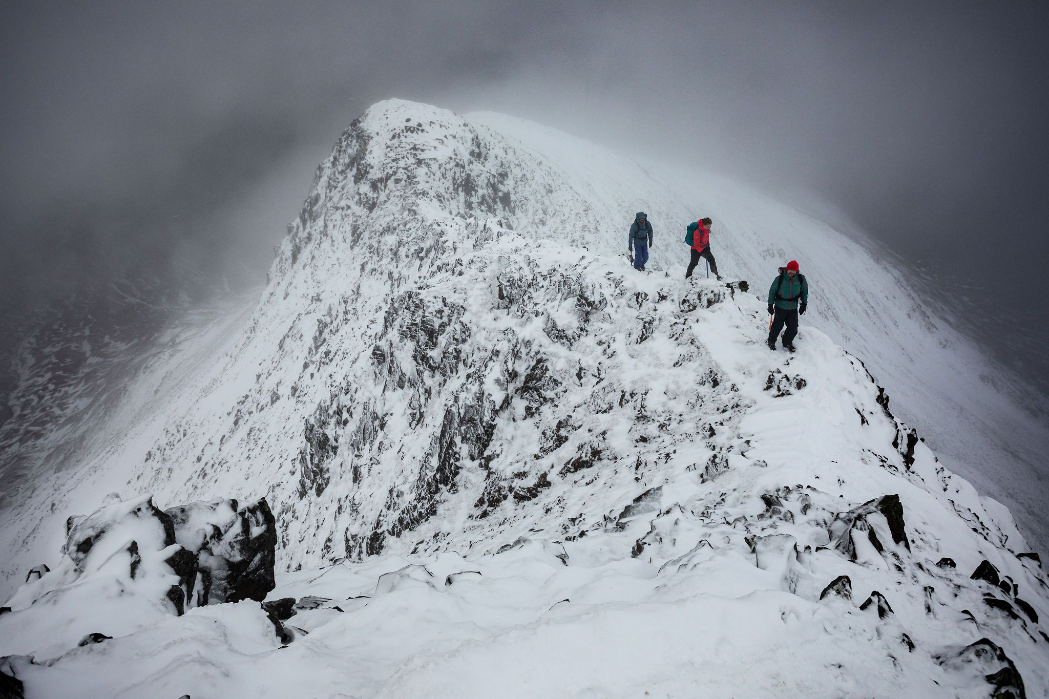 Winter hikers on snowy mountain ridge in the scottish highlands. Dramatic arctic misty scene the adventure photographers