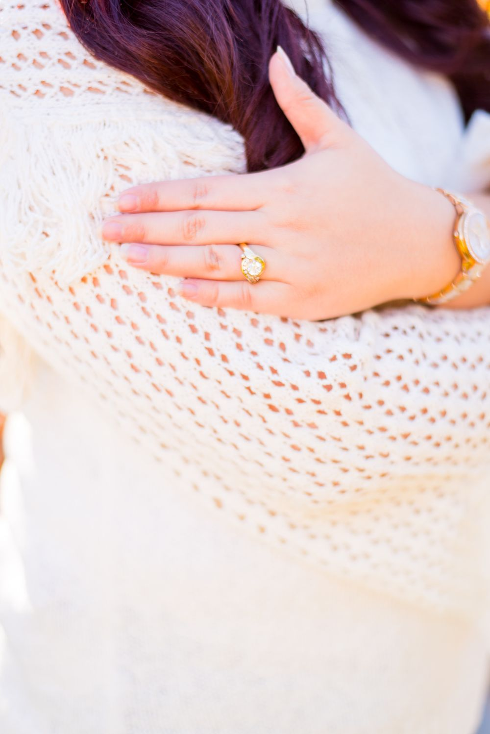 woman's hand with an engagement ring touching her arm in a white knitted sweater