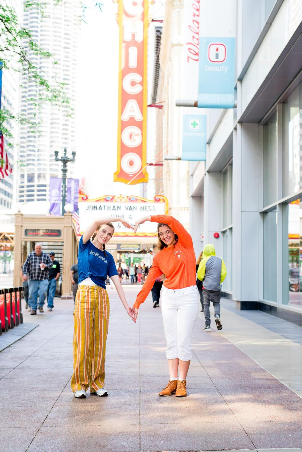 two senior girls in front of the Chicago Theater sign for Chicago senior pictures making a heart with their arms