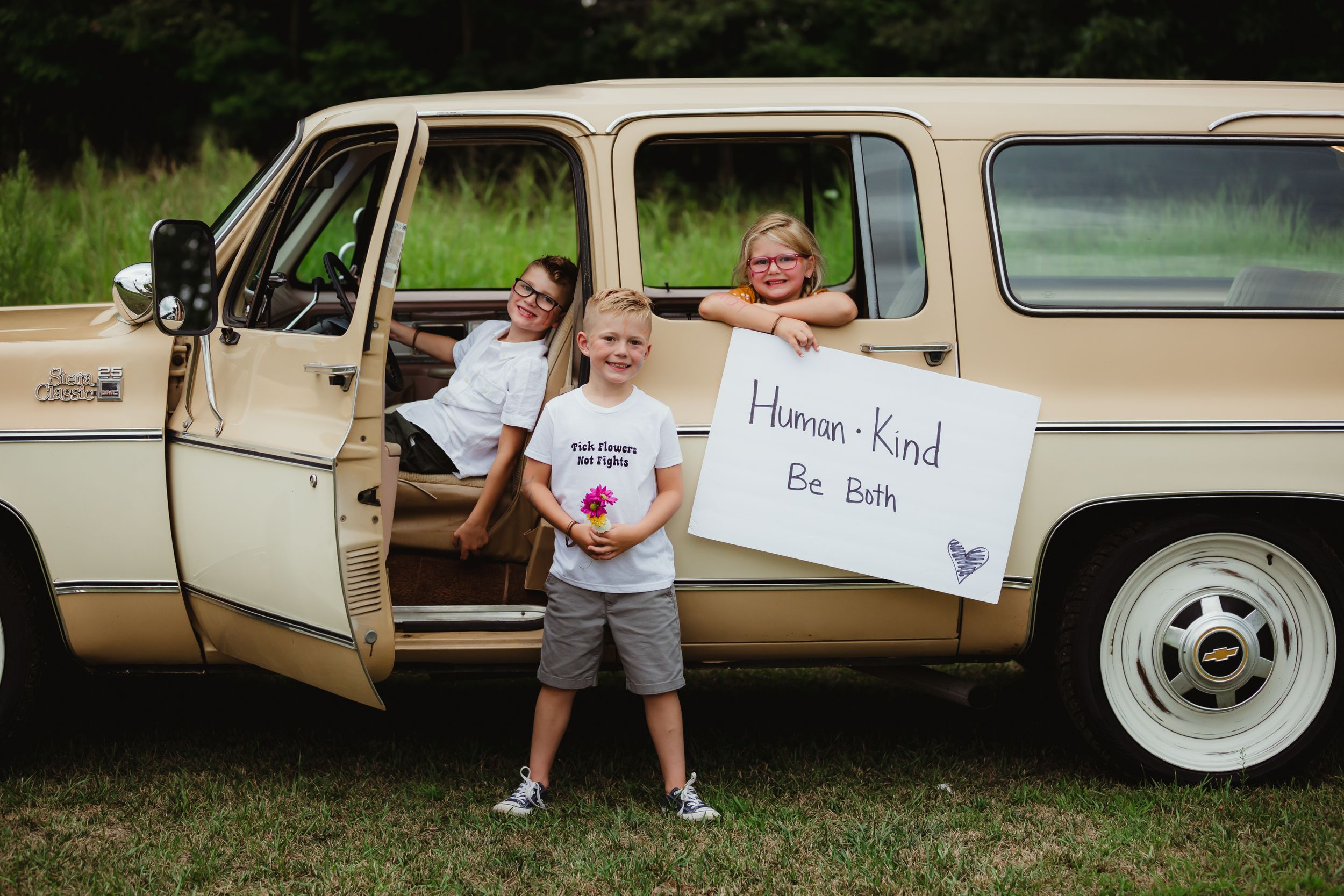 "Kids sitting in or standing in front of a station wagon with a sign ""human, kind, be both."""