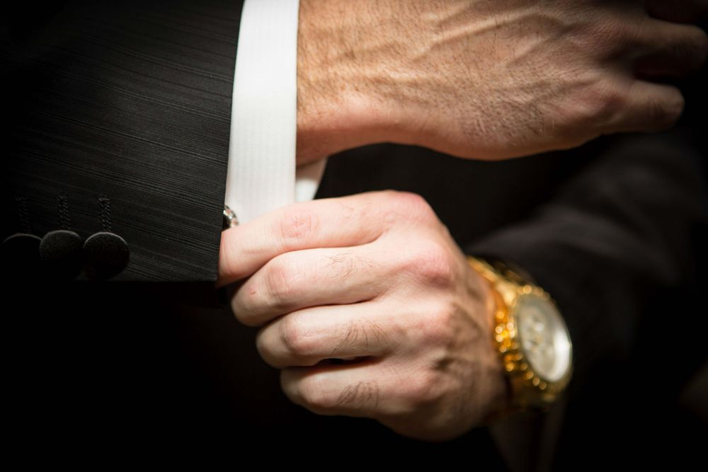 Close up picture of a groom adjusting his cuff links before his wedding.