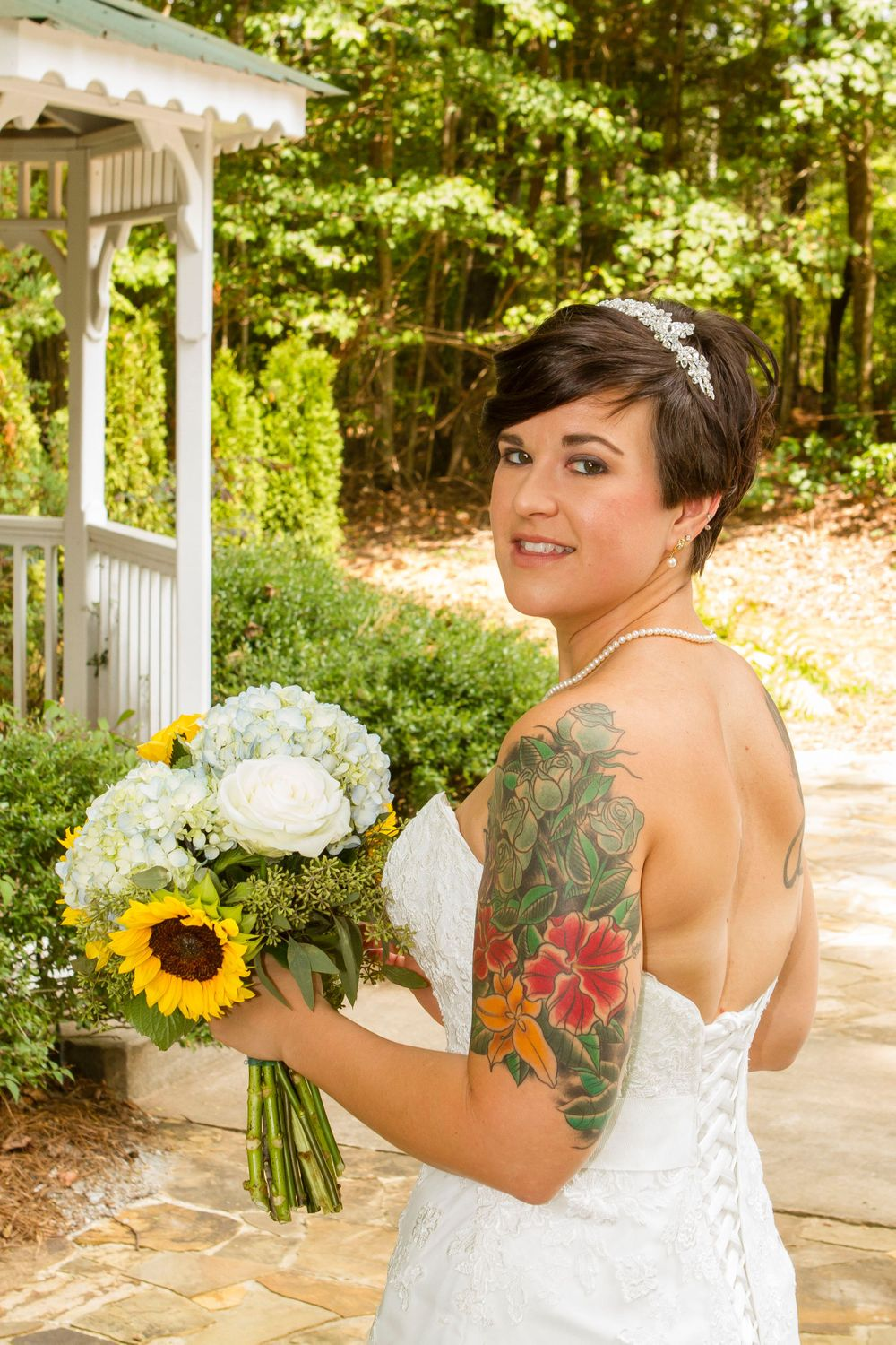 Outdoor tattooed bride with short hair looking over her shoulder while holding a bouquet of flowers.