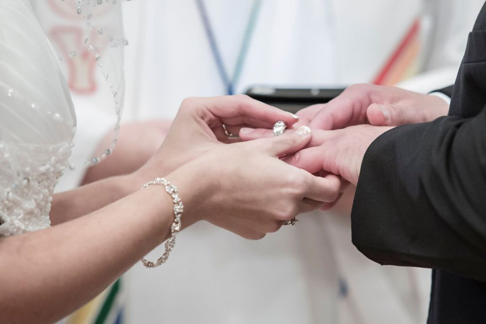 Close up picture of a bride slipping the ring on her new husbands hand during their wedding