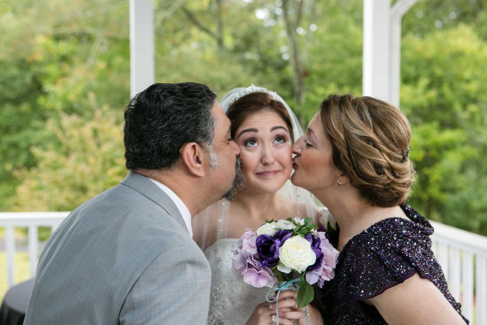 A bride's Mom and Dad kiss her cheeks